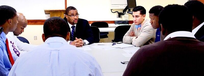 Group of young males engaged in discussion led by Dr. Cooper